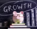 Pink piggy bank with glasses standing on books next to a blackboard with growth chart.